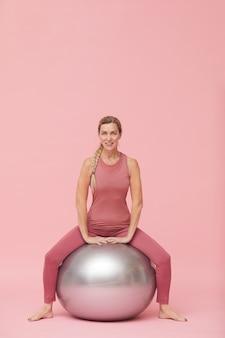 ピンクに対してフィットネス運動をしている成熟した女性