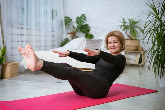 Mature woman doing fitness at home on the mat in sportswear