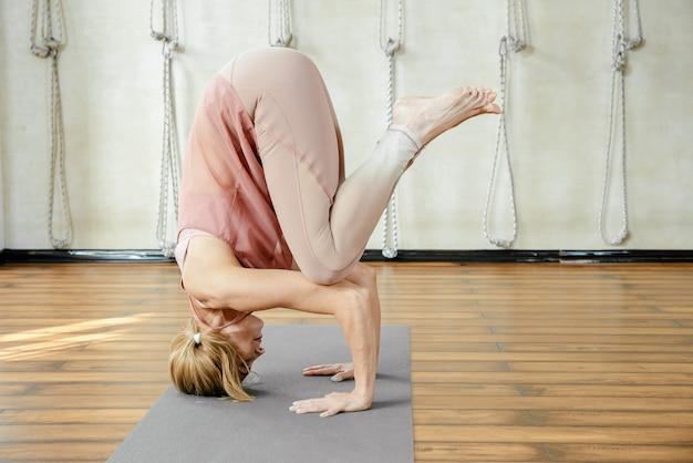 Зрелая женщина делает позу йоги стойка на голове в студии
