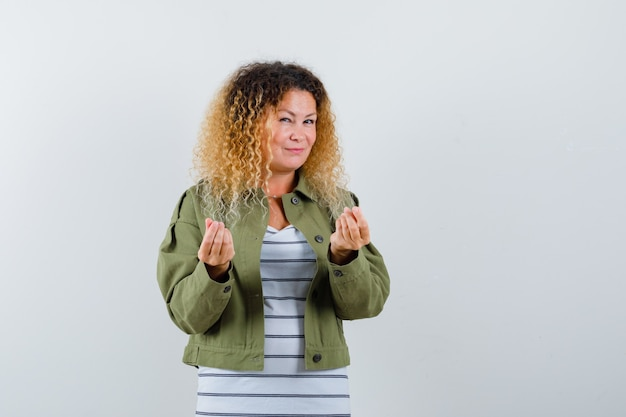 Mature woman doing italian gesture in green jacket, t-shirt and looking satisfied , front view.