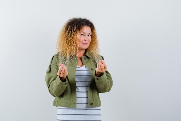 Зрелая женщина делает итальянский жест в зеленой куртке, футболке и выглядит довольным, вид спереди.