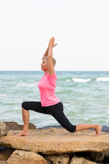 Mature woman doing pilates by the sea. vertical side view portrait