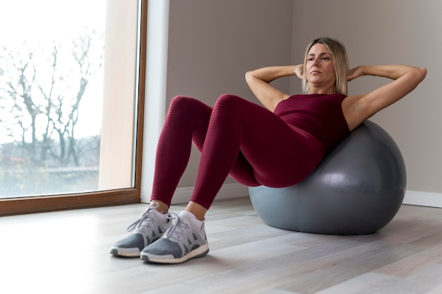 Mature woman doing sport exercises next to her window