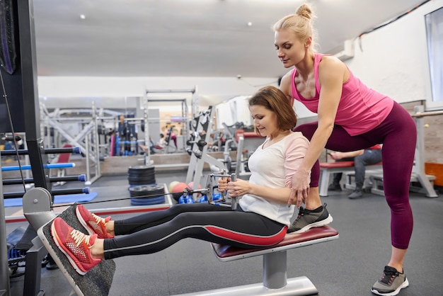 Mature woman doing sport exercises with personal trainer at gym