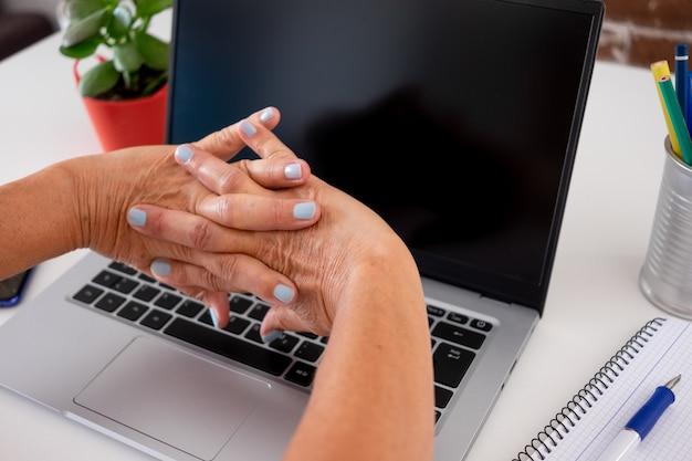 Зрелая женщина делает растяжку руками после использования портативного компьютера дома.
