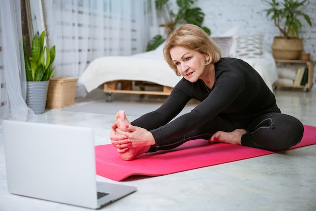 Mature woman doing workout on the mat online on laptop