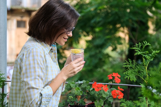 Питьевая вода зрелой женщины с лимоном. натуральный антиоксидант, диетический напиток, здоровье, первый утренний напиток, копия пространства