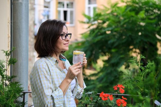 レモンと水を飲む成熟した女性。天然抗酸化物質、ダイエットドリンク、健康、ファーストモーニングドリンク、コピースペース