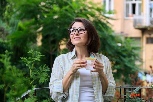 レモンと水を飲む成熟した女性。天然抗酸化物質、ダイエットドリンク、健康、最初の朝のドリンク