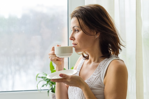 Mature woman drinks morning coffee
