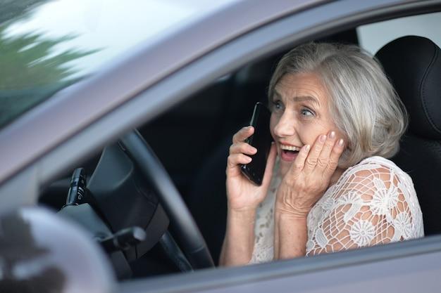 Зрелая женщина за рулем автомобиля и разговаривает по телефону