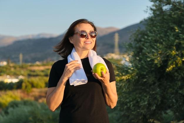 リンゴを食べる成熟した女性、女性の健康的なライフスタイル、スポーツと健康食品、日没の自然の背景