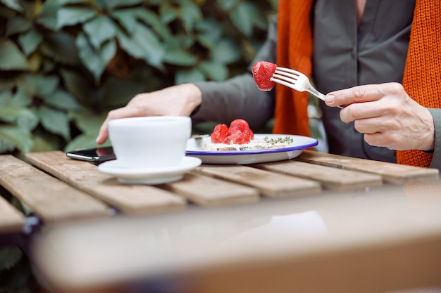 Mature woman eats toast with cream and strawberries taking mobile phone at table on outdoors