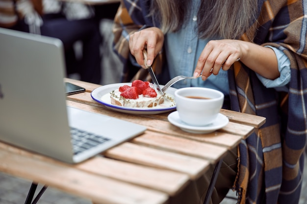 Mature woman eats toast with cut strawberries and cream at table on outdoors cafe terrace