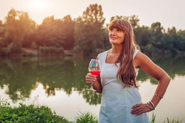 Mature woman enjoying glass of wine by river in autumn park,