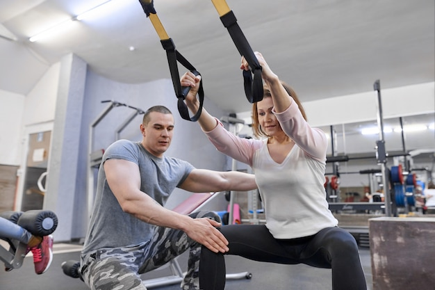 Зрелая женщина, осуществляющих в тренажерном зале, используя фитнес ремни петли