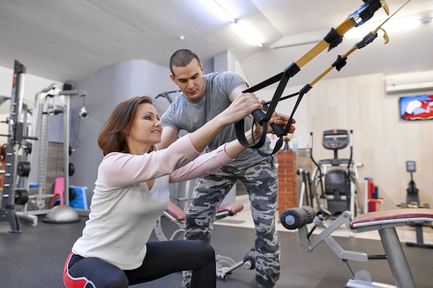 Зрелая женщина, осуществляющих в тренажерном зале, используя фитнес ремни петли.