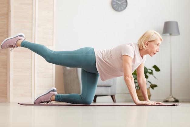 自宅の部屋でエクササイズマットの上に床で運動する成熟した女性