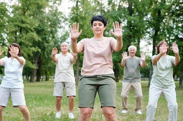 Зрелая женщина тренируется вместе с другими людьми во время тренировки в парке