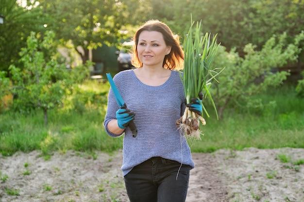 Зрелая женщина-фермер гуляет по саду с зеленым свежим луком