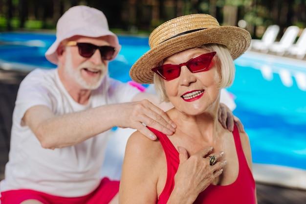 Зрелая женщина чувствует себя счастливой, проводя время с заботливым мужем, загорая вместе