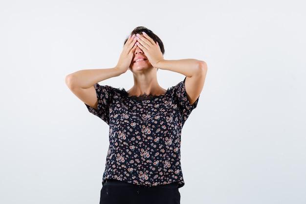Donna matura in camicetta floreale, gonna nera che copre gli occhi con le mani e sembra allegro, vista frontale.