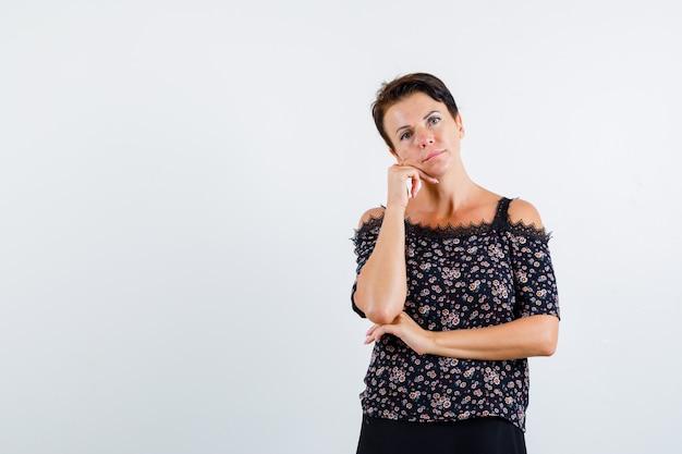 Donna matura in camicetta floreale e gonna nera con il mento pendente a portata di mano, tenendo una mano sotto il gomito e guardando pensieroso, vista frontale.