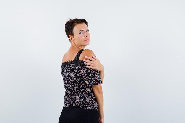 Donna matura in camicetta floreale e gonna nera guardando sopra la spalla mentre posa e sembra attraente, vista frontale.
