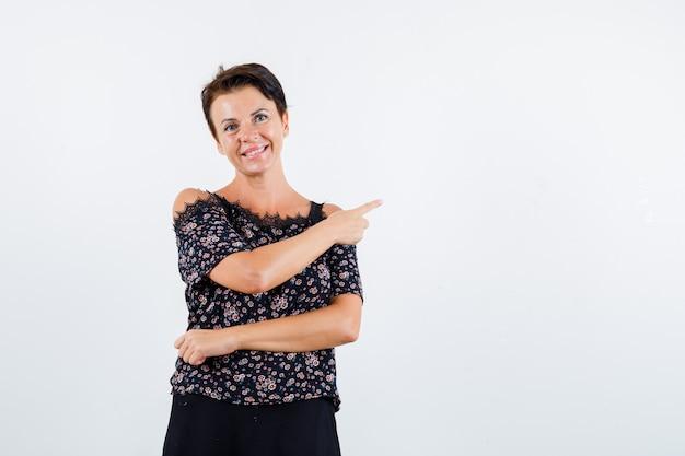 Donna matura in camicetta floreale e gonna nera che punta a destra con il dito indice e sembra allegra, vista frontale.