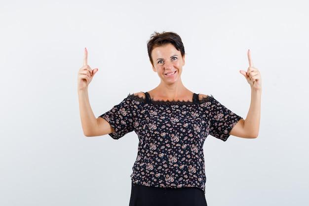 Donna matura in camicetta floreale e gonna nera rivolta verso l'alto con il dito indice e guardando allegro, vista frontale.