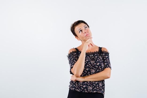Donna matura in camicetta floreale e gonna nera appoggiando la mano sul mento tenendo la mano sotto il gomito e guardando pensieroso, vista frontale.