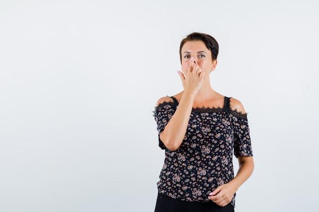 Donna matura in camicetta floreale e gonna nera tirando il naso verso l'alto con le dita e guardando serio, vista frontale.
