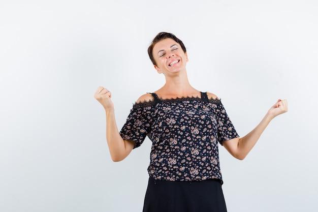 Donna matura in camicetta floreale e gonna nera che mostra il gesto del vincitore e sembra fortunato, vista frontale.