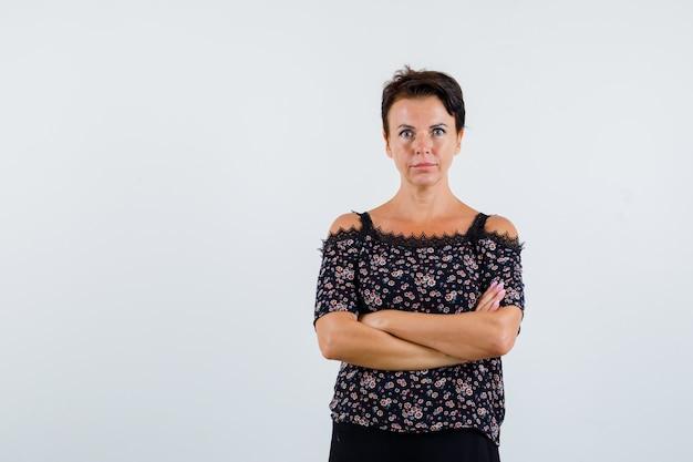 Donna matura in camicetta floreale e gonna nera in piedi con le braccia incrociate e guardando serio, vista frontale.