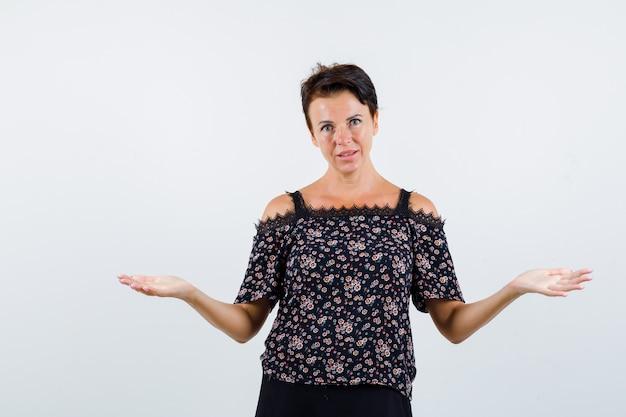 Donna matura in camicetta floreale e gonna nera che allunga le mani in modo interrogativo e sembra confuso, vista frontale.