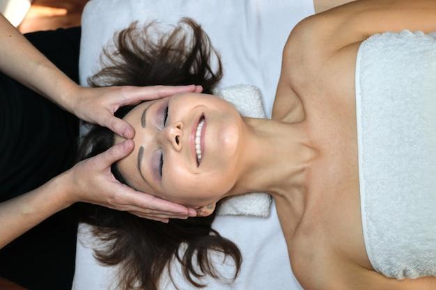 성숙한 여성은 뷰티 스파 살롱에서 얼굴과 목 마사지를 받습니다. 미용, 트리트먼트, 헬스케어, 페이스&바디 스킨케어, 중년 여성