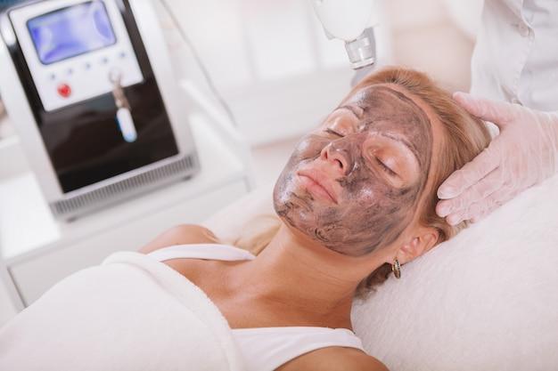 Зрелая женщина получает уход за кожей лица в салоне красоты