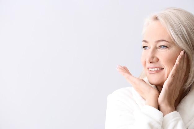 Зрелая женщина делает себе массаж лица