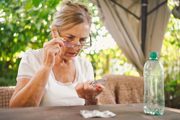 Mature woman in glasses hold pills read medicine instruction on packaging before take meds