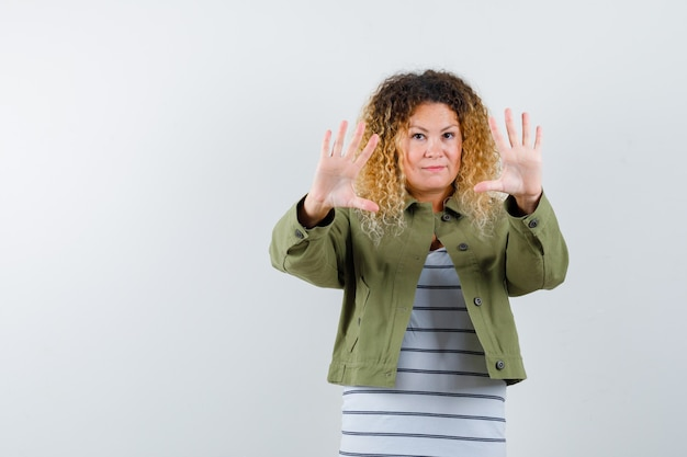 Mature woman in green jacket, t-shirt showing refusal gesture and looking confident , front view.