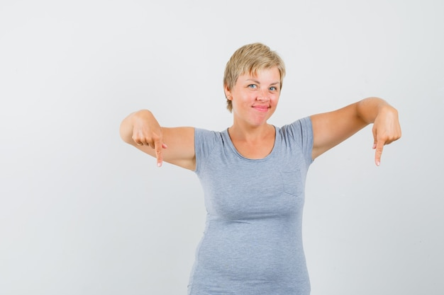 Mature woman in grey t-shirt pointing down and looking confident