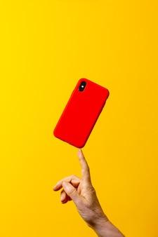 黄色の背景に1本の指で赤いスマートフォンケースを持っている成熟した女性の手