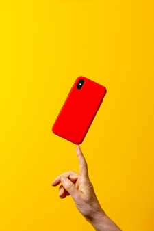 Mature woman hand holding a red smartphone case with one finger against a yellow background