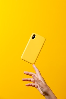 Mature woman hand holding a yellow smartphone with  a yellow case with one finger against a yellow background