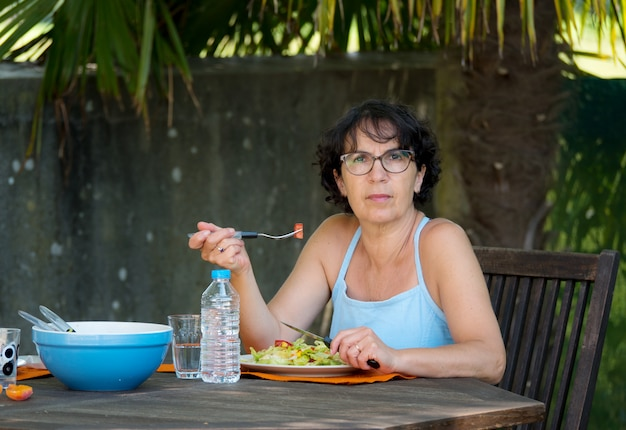 Mature woman having lunch in the garden