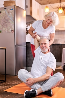 Mature woman help her husband to stretch arms, support him from back, at home on the floor
