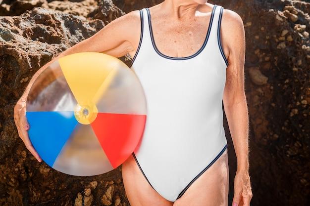 Donna matura che tiene in mano un pallone da spiaggia mentre indossa un costume da bagno
