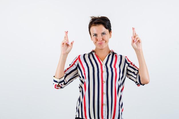 Donna matura tenendo le dita incrociate in camicetta a righe e guardando fiducioso. vista frontale.