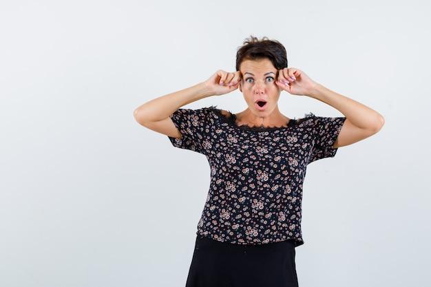 Donna matura che tiene i pugni vicino alla testa, tenendo la bocca aperta in camicetta floreale e gonna nera e guardando sorpreso. vista frontale.