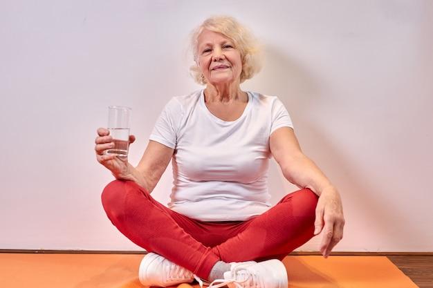 바닥에 요가 운동 후 신선한 물 잔을 들고 성숙한여 인, 휴식을 취하십시오. 건강한 라이프 스타일 컨셉